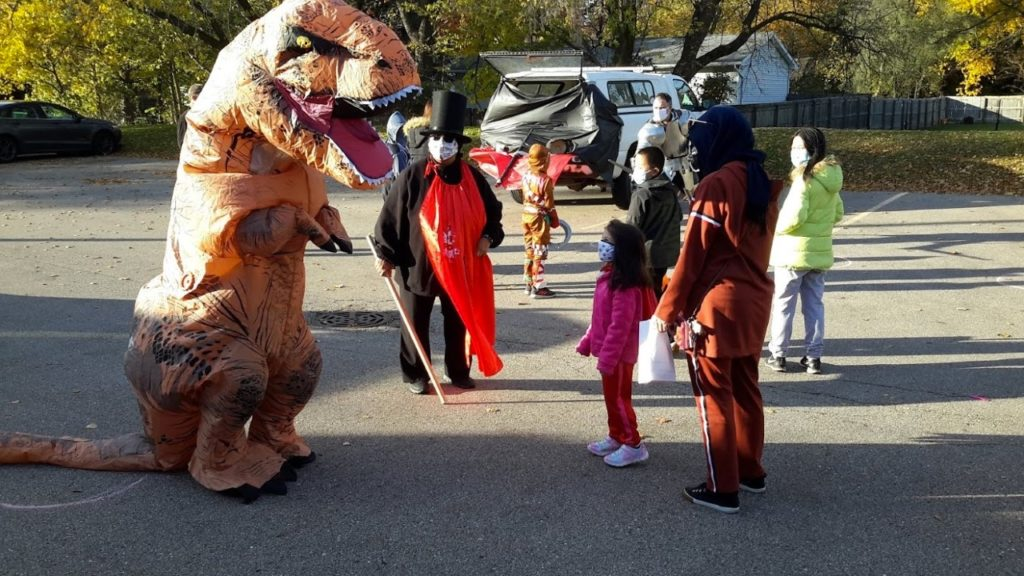 Librariosaurus and staff members Hung Wu and Andrea Rodriguez entertain at Trunk n Treat. Donations pay for the candy at this event.