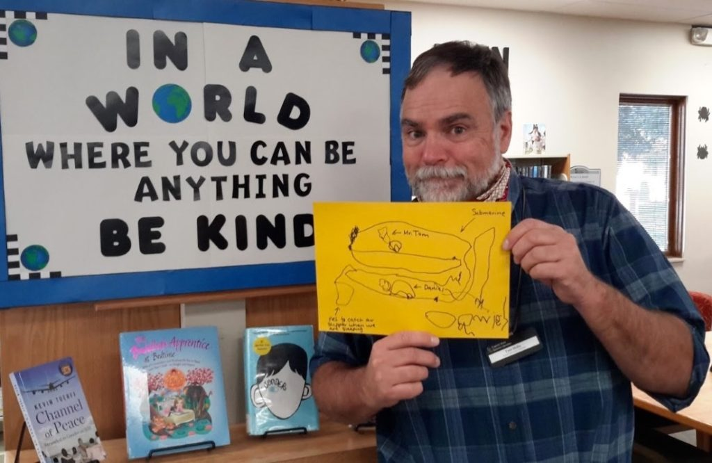 Youth Librarian Tom Shilts with a drawing made by a Storytime attendee. (Friends pay for craft supplies used at Storytime.)