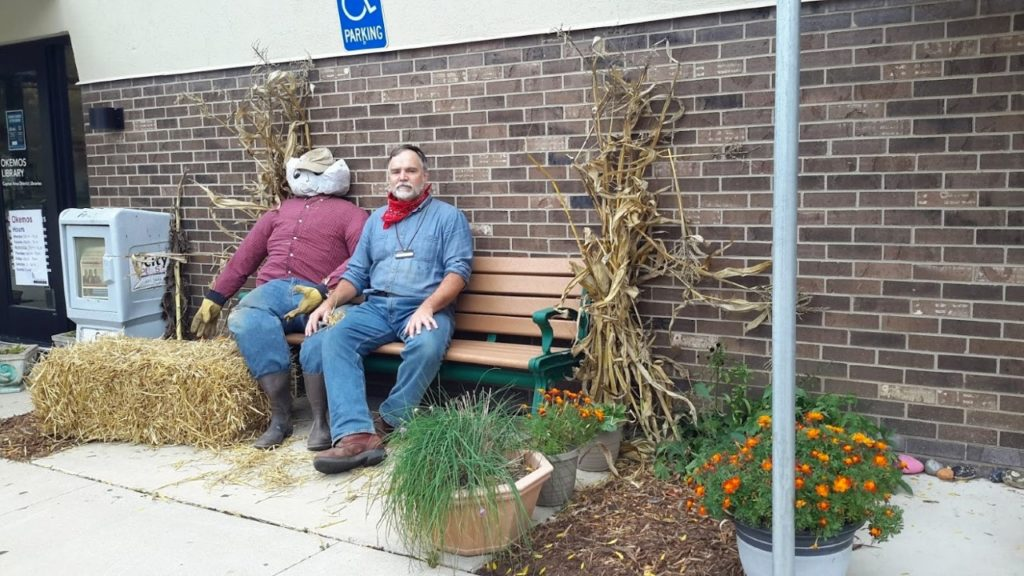 Youth Librarian Tom Shilts and a friend enjoy a fall day. (Donations paid for supplies to make the scarecrow.)